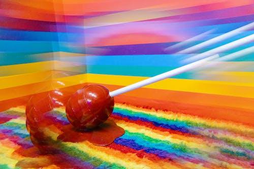 Brown and White Lollipop on Multi Color Striped Textile