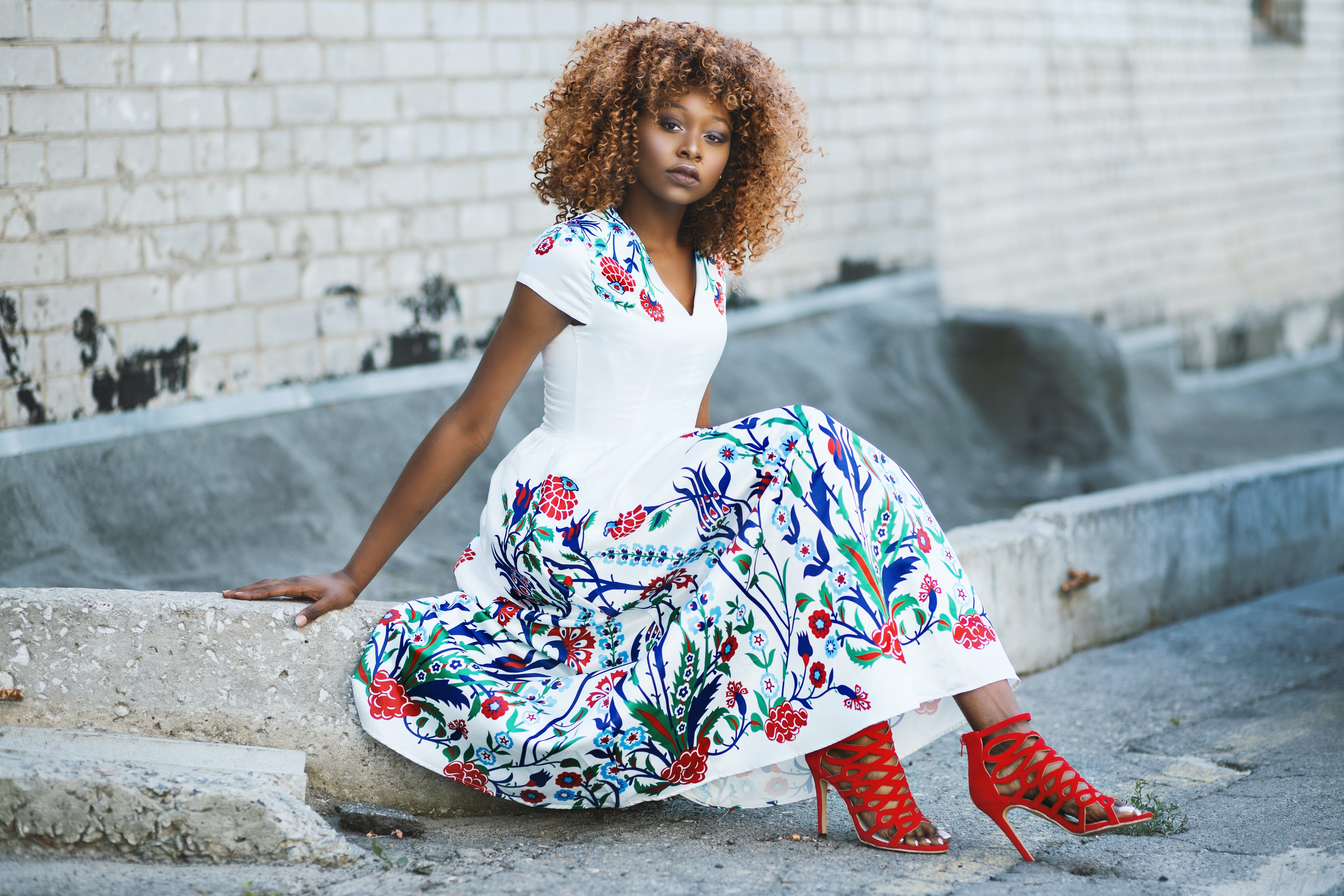 Woman in White and Multicolored Floral Flare Dress Sitting on Concrete