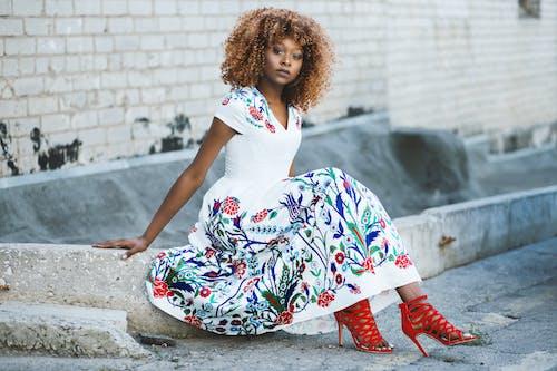 坐在混凝土上的白色和五彩花喇叭裙的女人