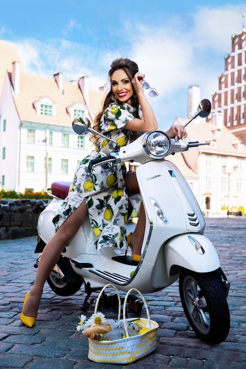 Woman in Black and White Floral Dress Riding on White Motor Scooter