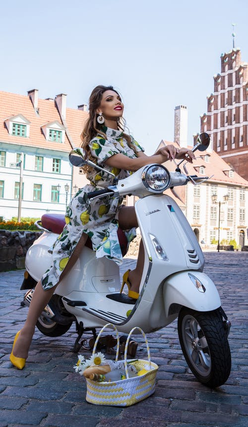 Woman in White and Pink Floral Dress Riding on White Motor Scooter