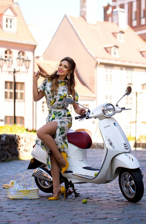 Woman in Green and Brown Floral Dress Riding White Motor Scooter
