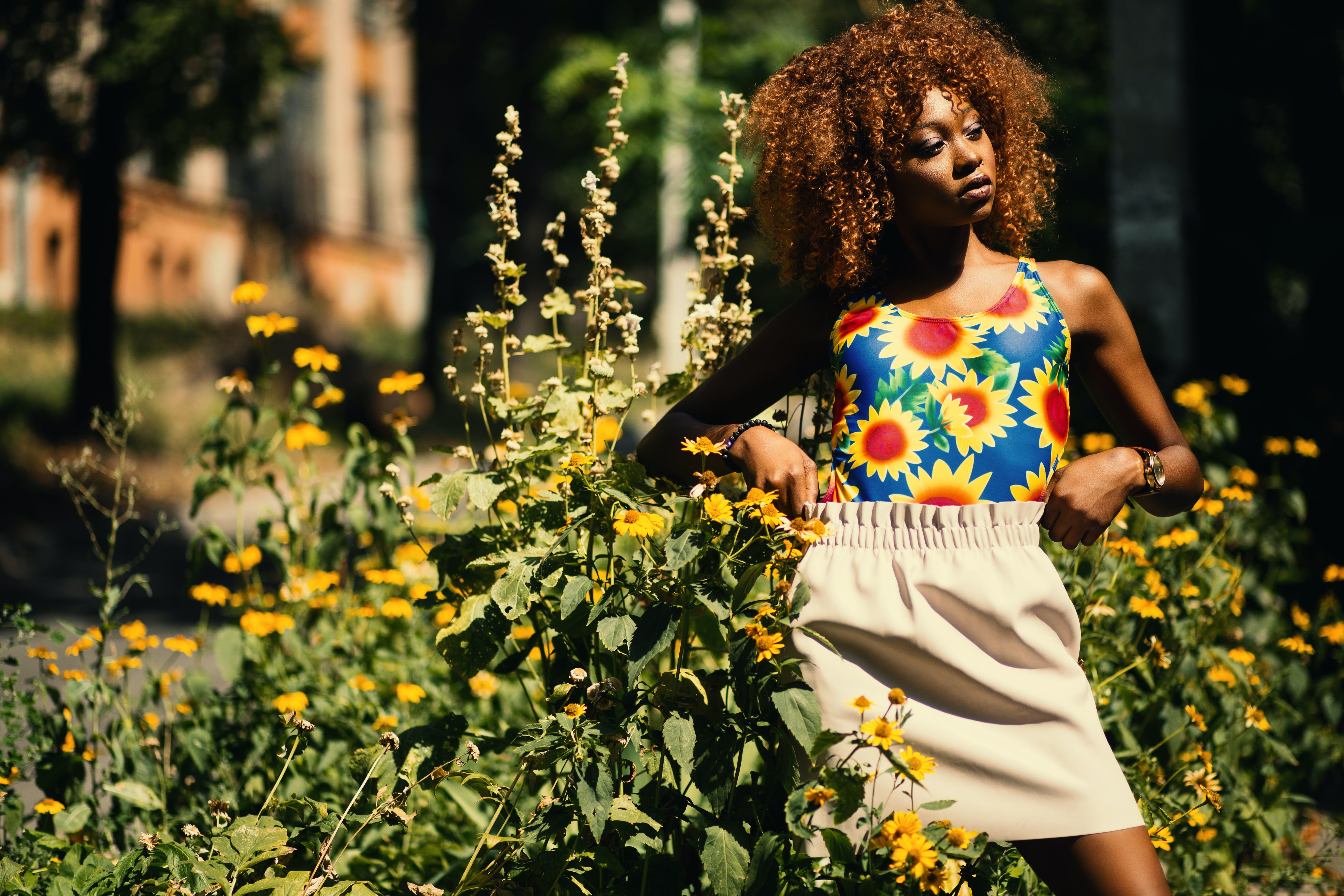 Photography of Woman Wearing Blue, Yellow and Red Floral Tank Top Standing