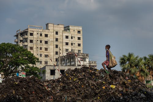 Child on Top of Pile of Garbage