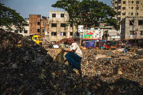 Person Collecting Trash on Pile of Garbage