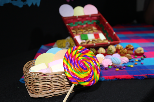 Close Up Photo of Lolipop Beside Woven Basket