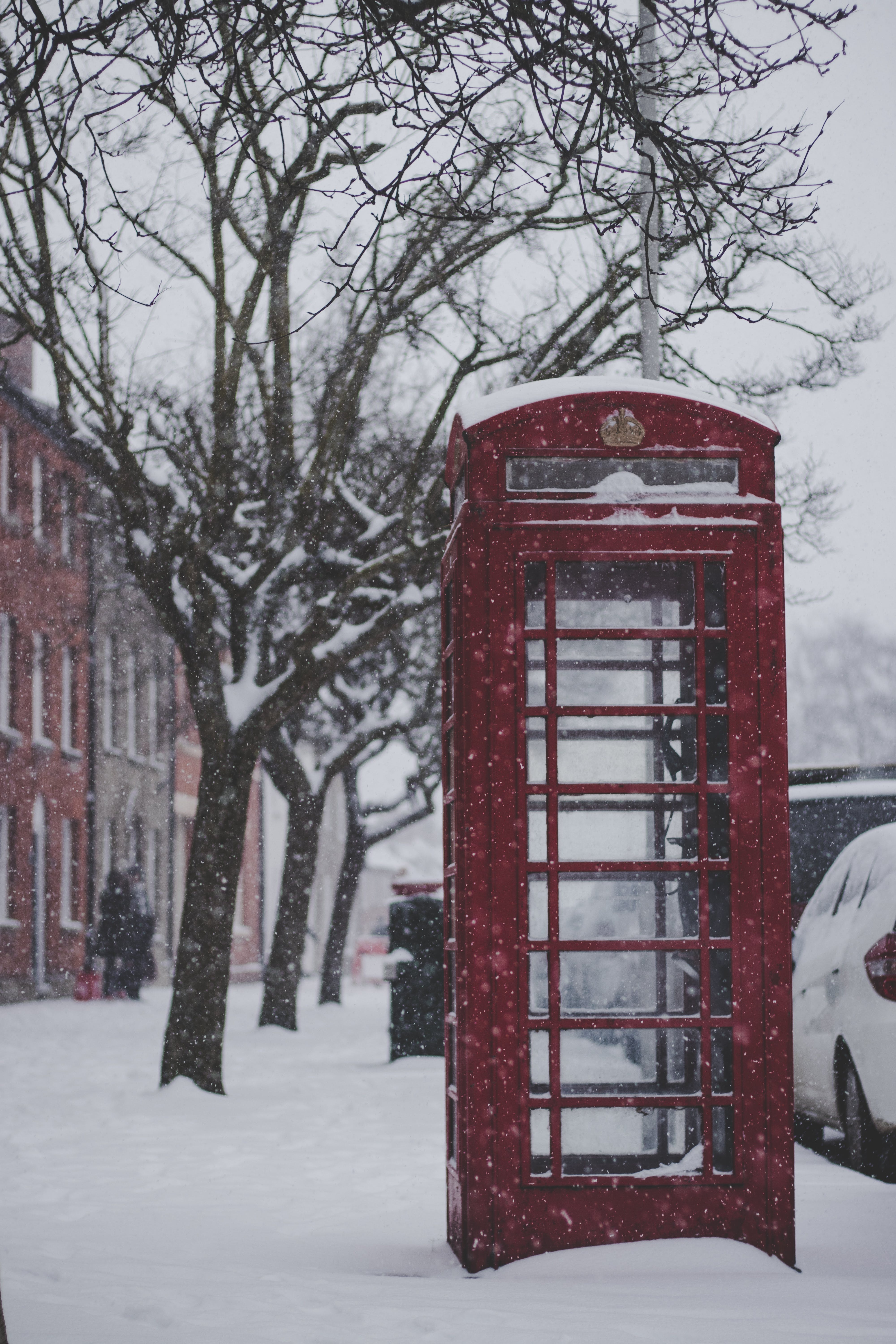 Red Telephone Booth on the Sidewalk With Snow