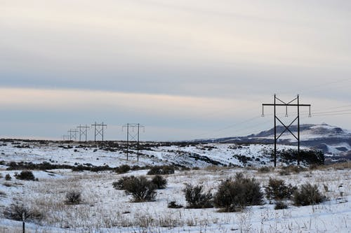 Landscape Photography of Snow-coated Ground With Utility Posts