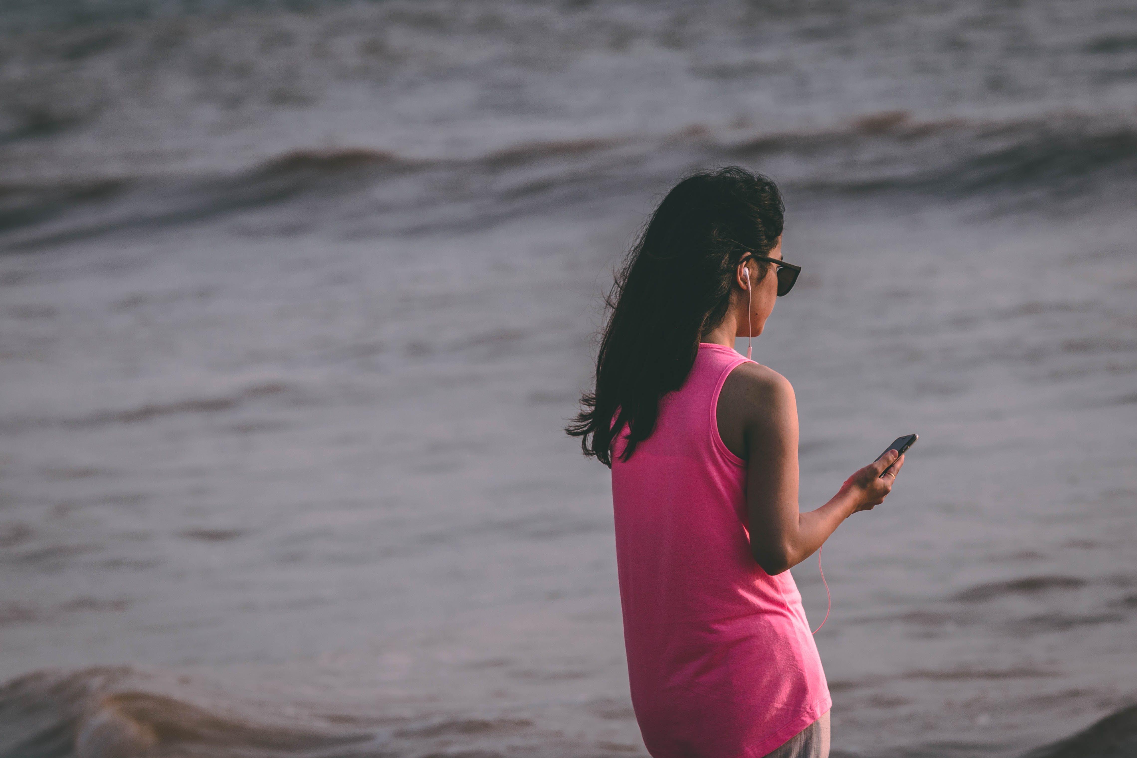 Woman Wearing Pink Tank Top Standing Near Sea Shore
