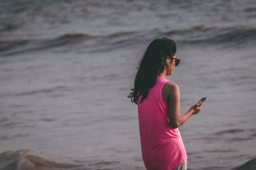 Woman Wearing Pink Tank Top Standing Near Sea Shore