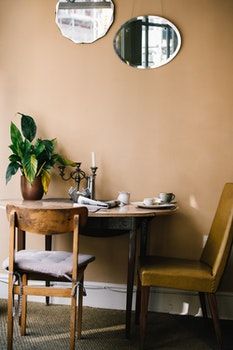 Round Brown Wooden Table With Two Brown Chairs