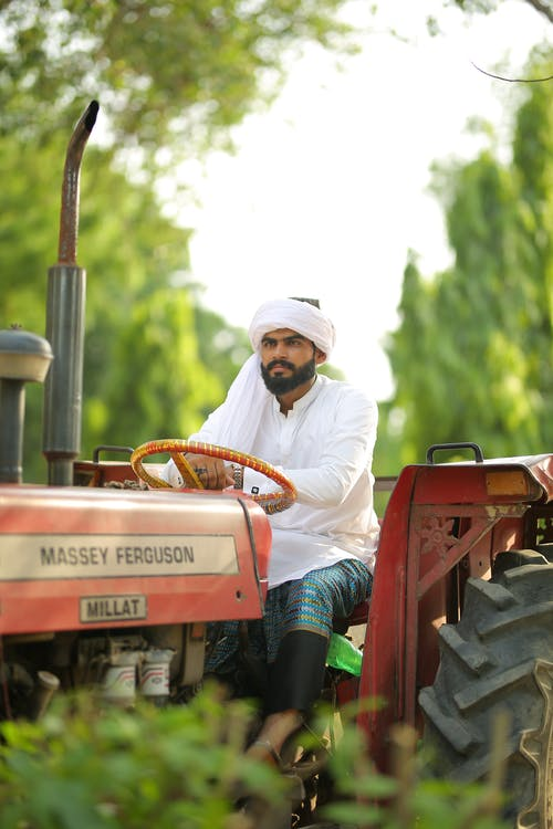 Man in White Thobe Riding Red Tractor