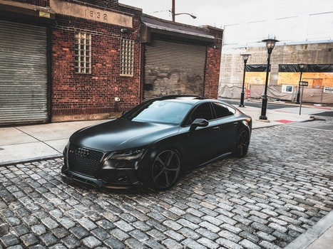 Black Audi A-series Parked Near Brown Brick House
