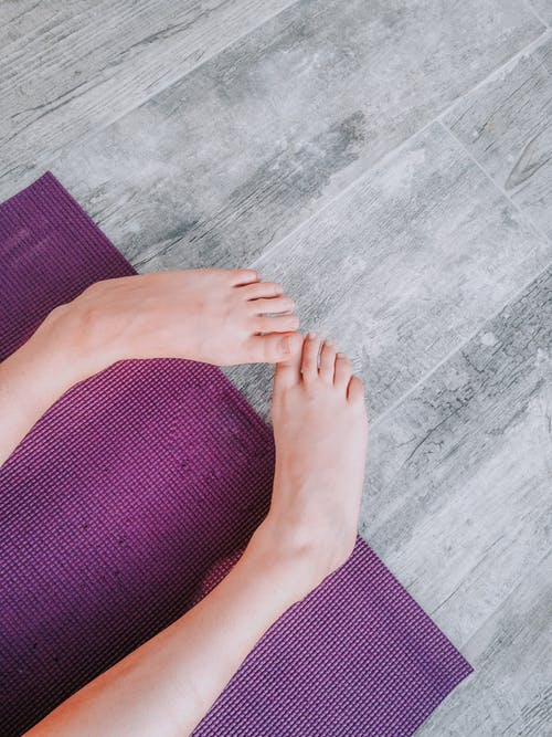 Person Lying on Purple Yoga Mat