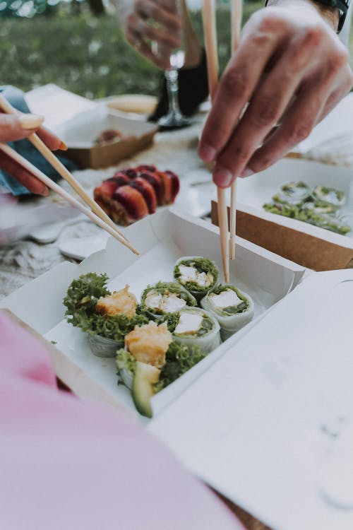 Person Holding Chopsticks With Food on White Ceramic Plate