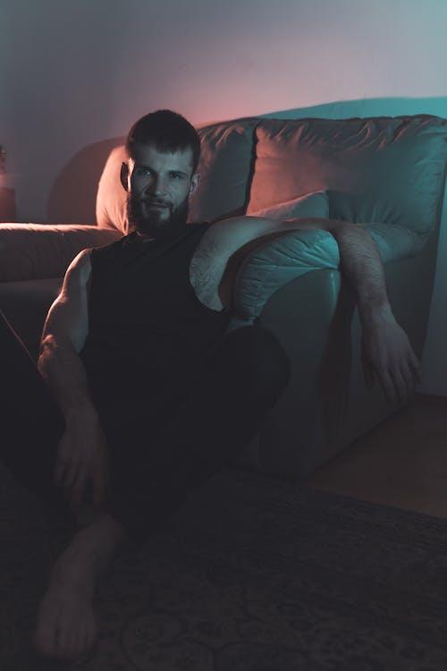 Man in Black Crew Neck T-shirt Sitting on Blue Sofa