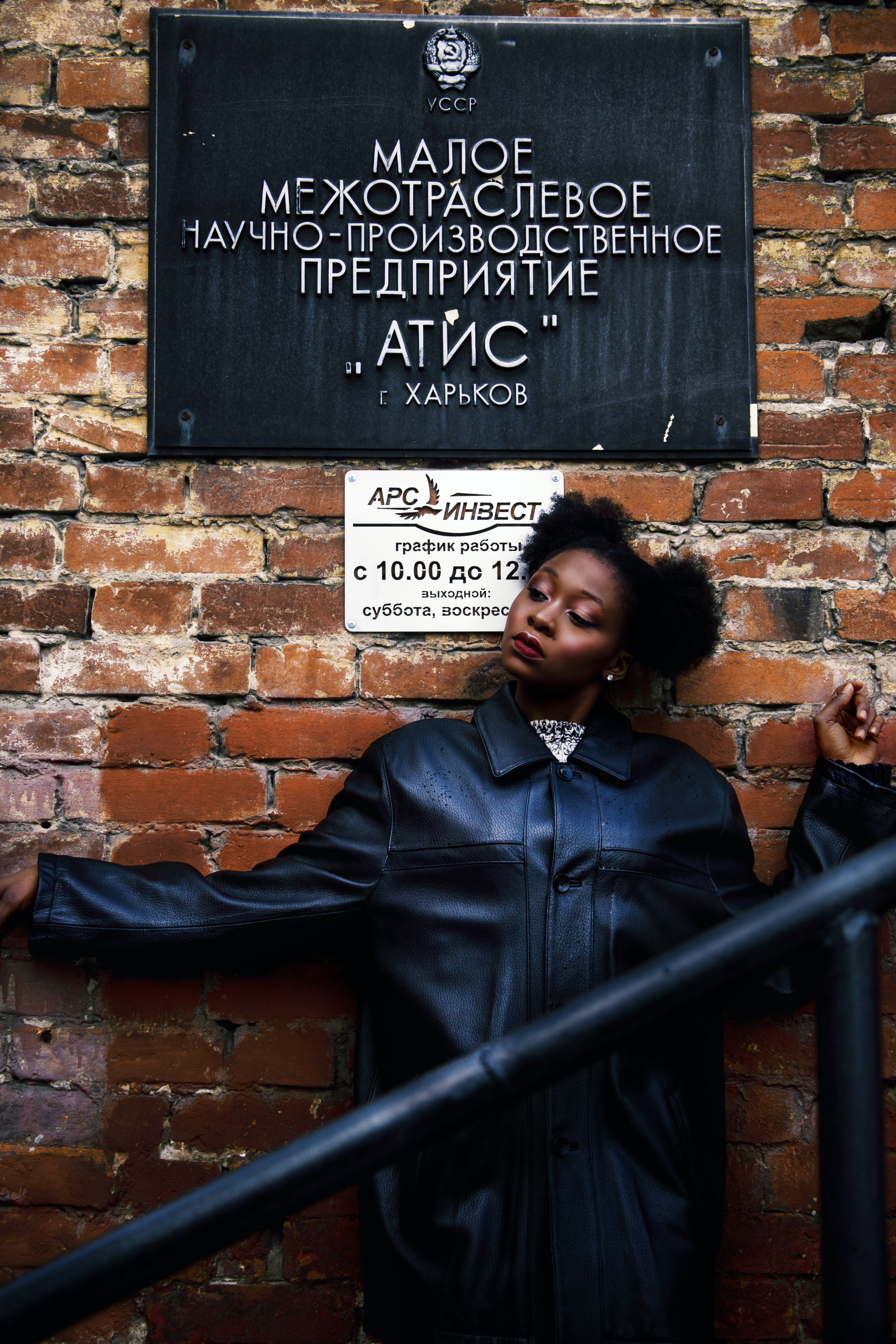 Woman in Black Leather Coat Leaning on Brick Wall
