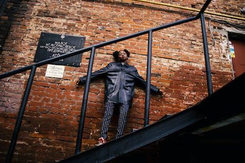 Gratis stockfoto met Afro-Amerikaanse vrouw, architectuur, bakstenen, bakstenen muur