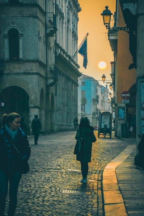 Photo of People Walking on Cobblestone Street