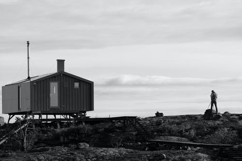 Grayscale Photo of Wooden House on Hill