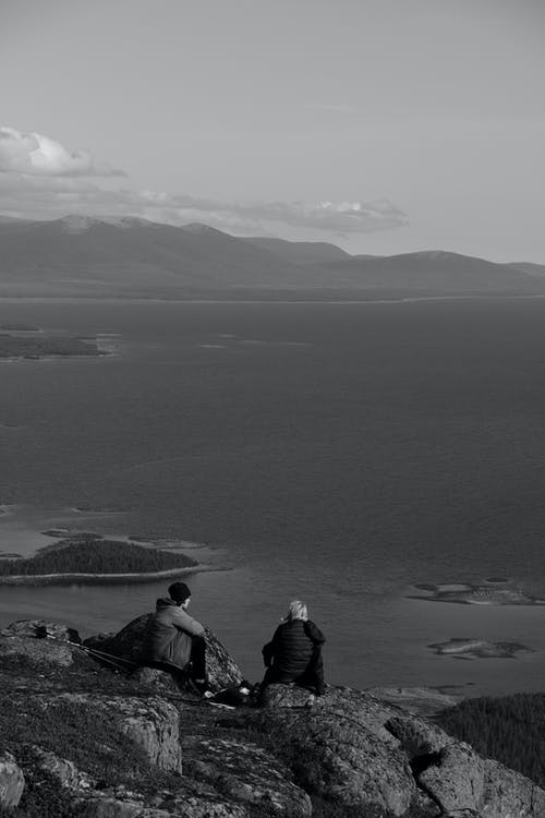 Grayscale Photo of 2 Person Sitting on Rock Near Body of Water