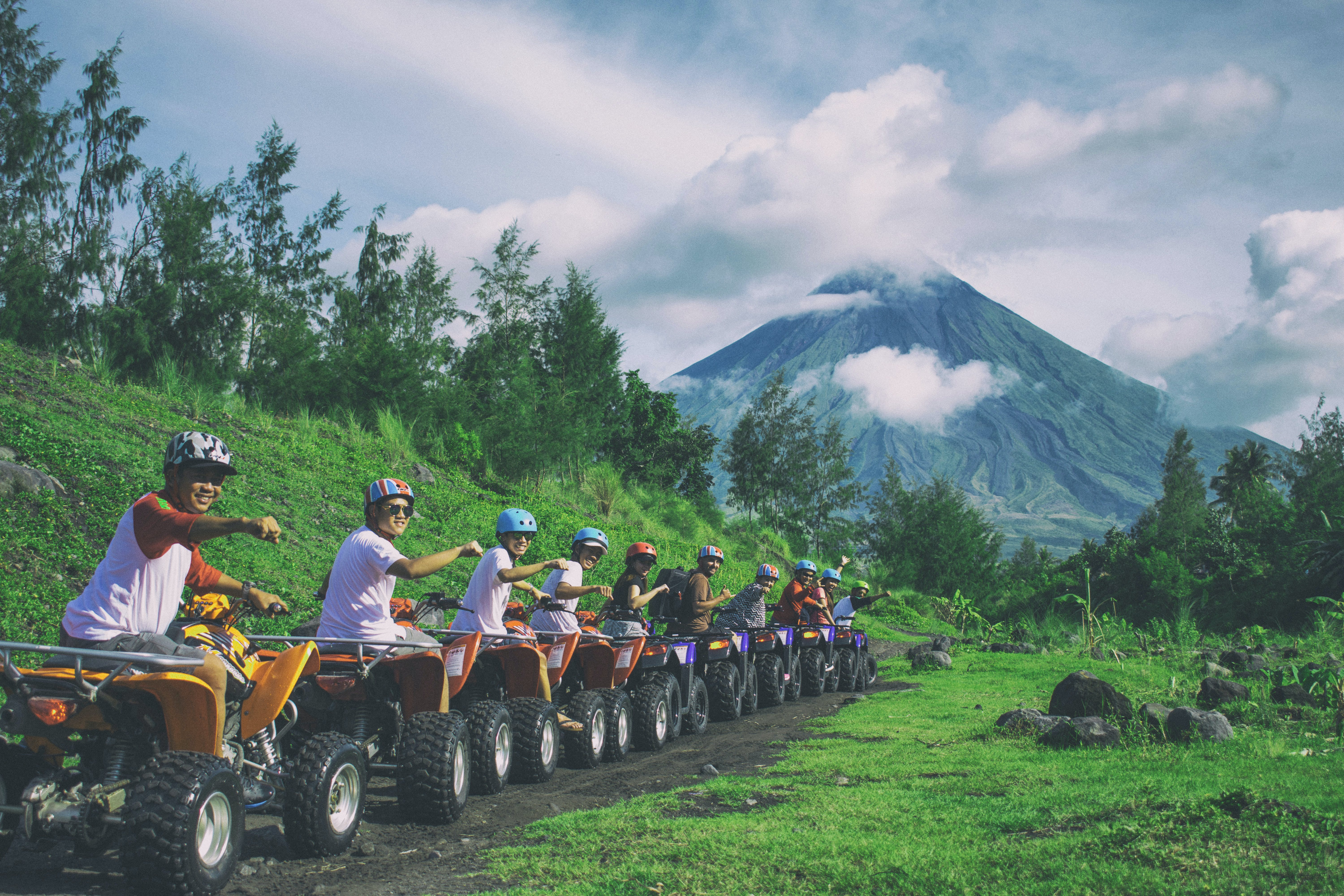 Line Of Men Riding On All Terrain Vehicles Holding Out Hand In A Fist