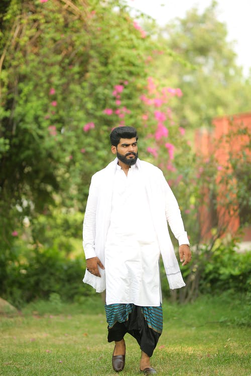 Man in White Long Sleeve Shirt Standing on Green Grass Field