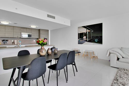Brown Dining Table with Chairs Wrapped in Black Fabric