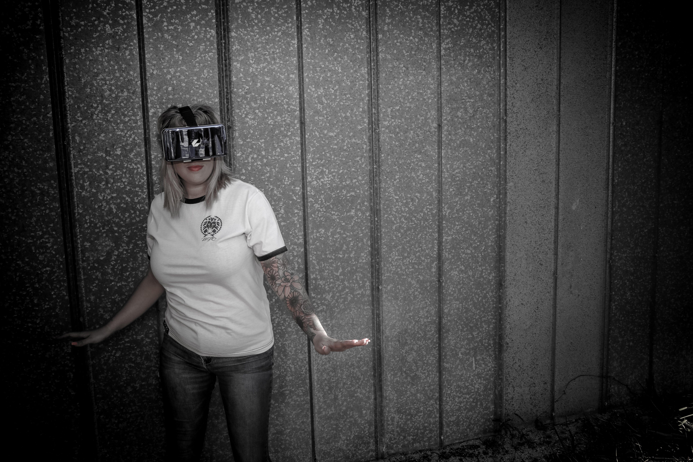 Woman Wearing Virtual Reality Headset Standing Beside Wall