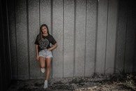 Woman Wearing Black Shirt and Daisy Dukes Leaning on Wall