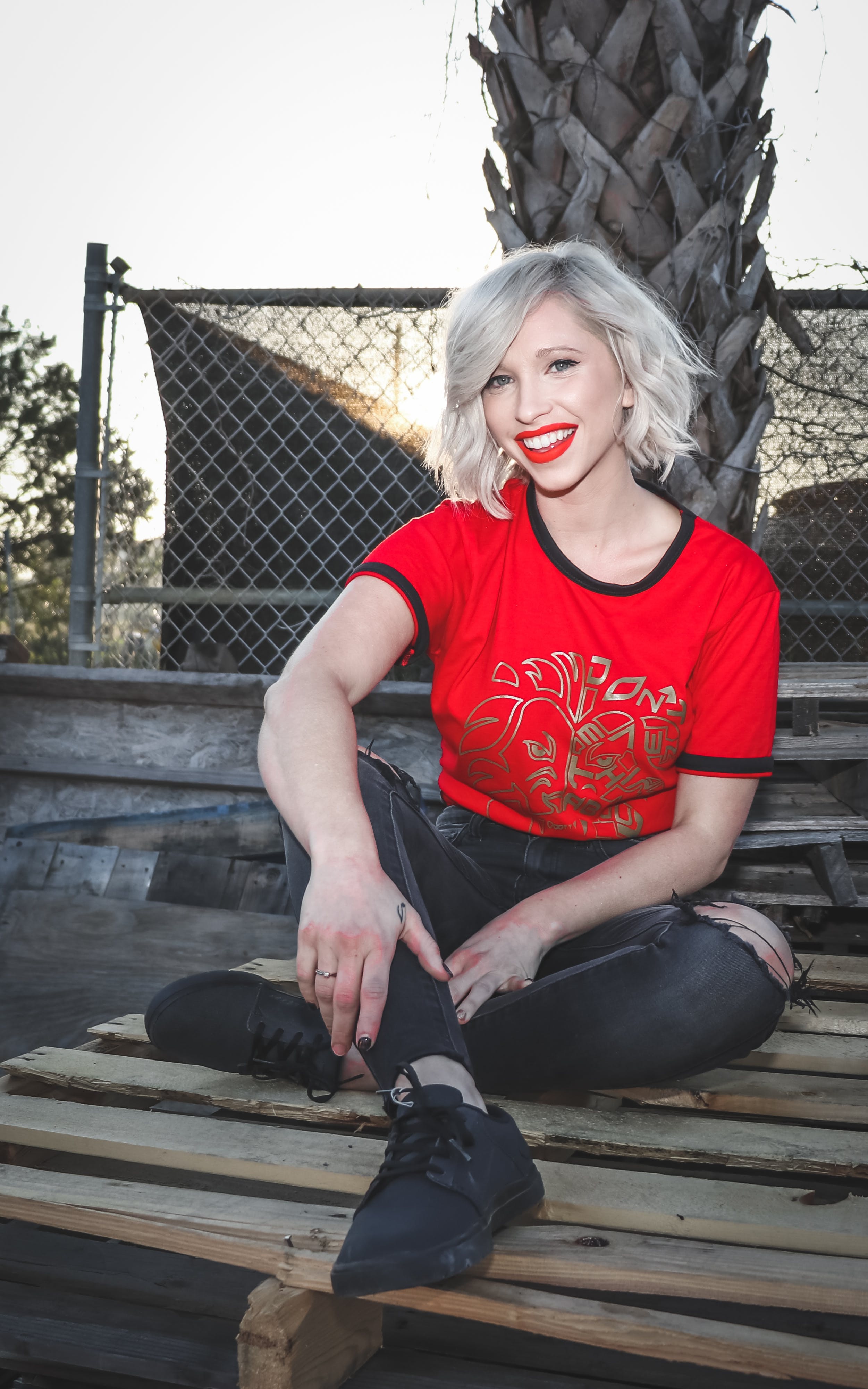 Woman Sit on Pallet Wearing Crew-neck T-shirt and Distressed Black Fitted Jeans