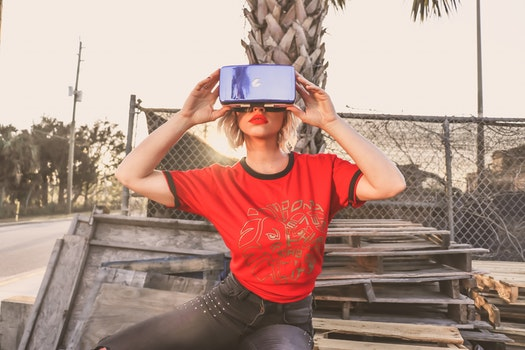 Woman in Red Crew-neck T-shirt Wearing Virtual Reality Glasses