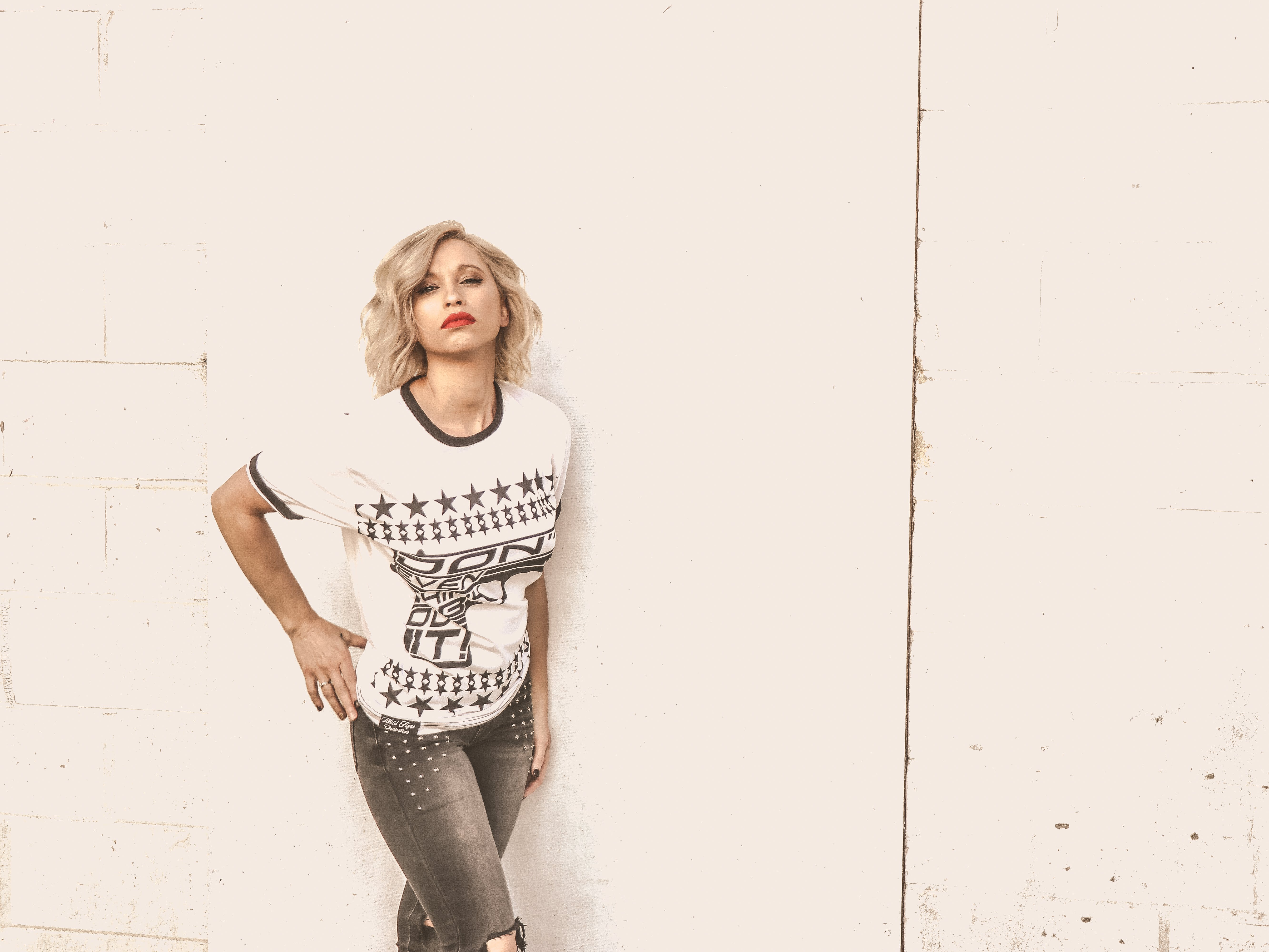 Woman With Blond Hair Wearing Whit Crew Neck Shirt and Gray Jeans