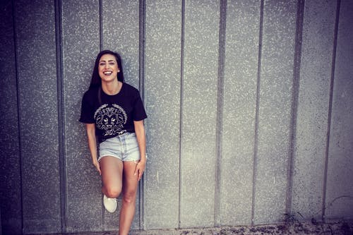Woman Wearing Black and White Crew-neck T-shirt and Gray Denim Short Shorts Outfit Leaning on Gray Wall