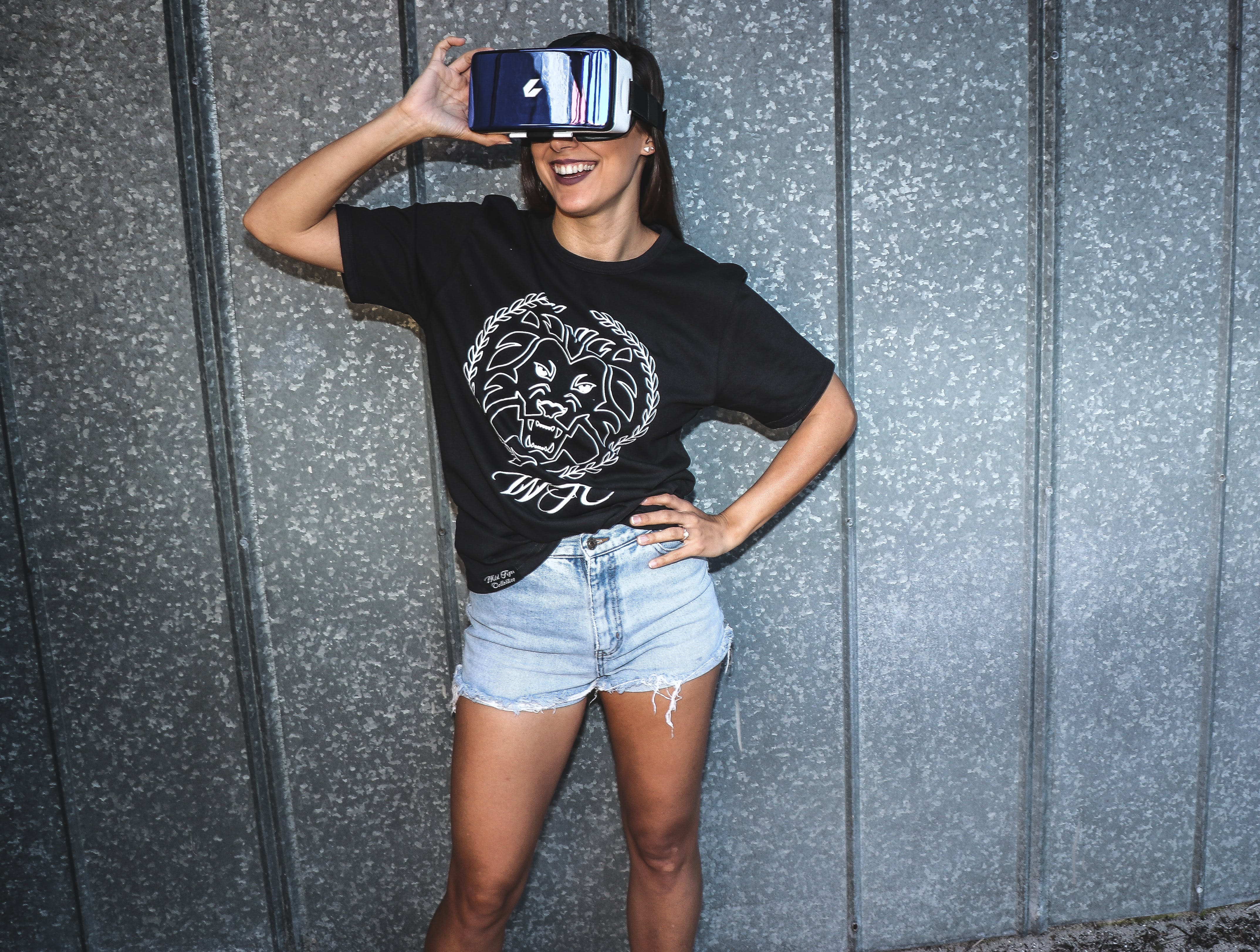 Woman in Black T-shirt Standing and Smiling While Using a Virtual Reality Glasses