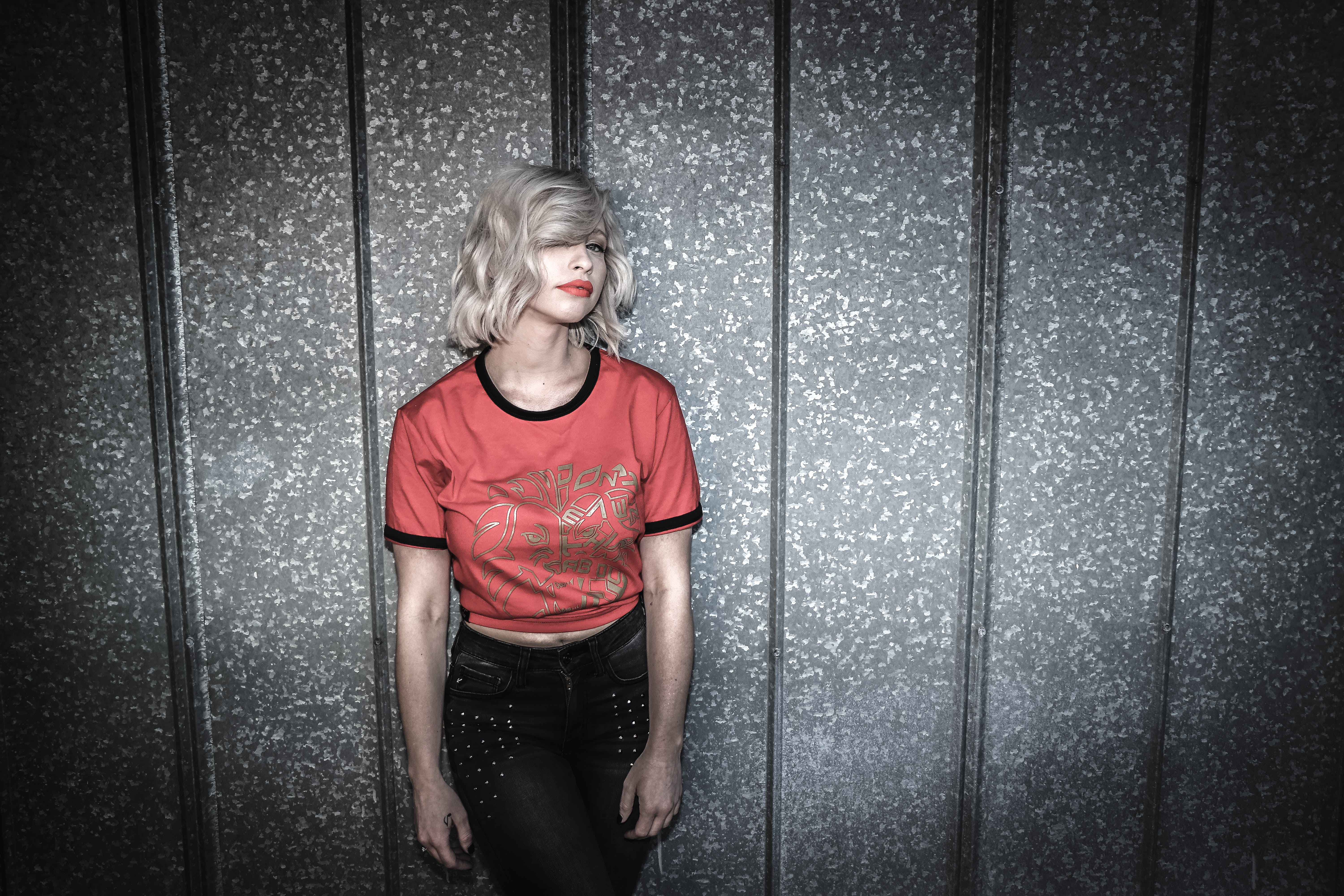 Woman Wearing Red and Black Scoop-neck Shirt and Black Bottoms Leaning on Gray Wall