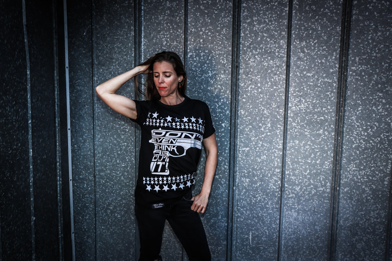Woman Wearing Black Shirt and Pants Near Gray Wall