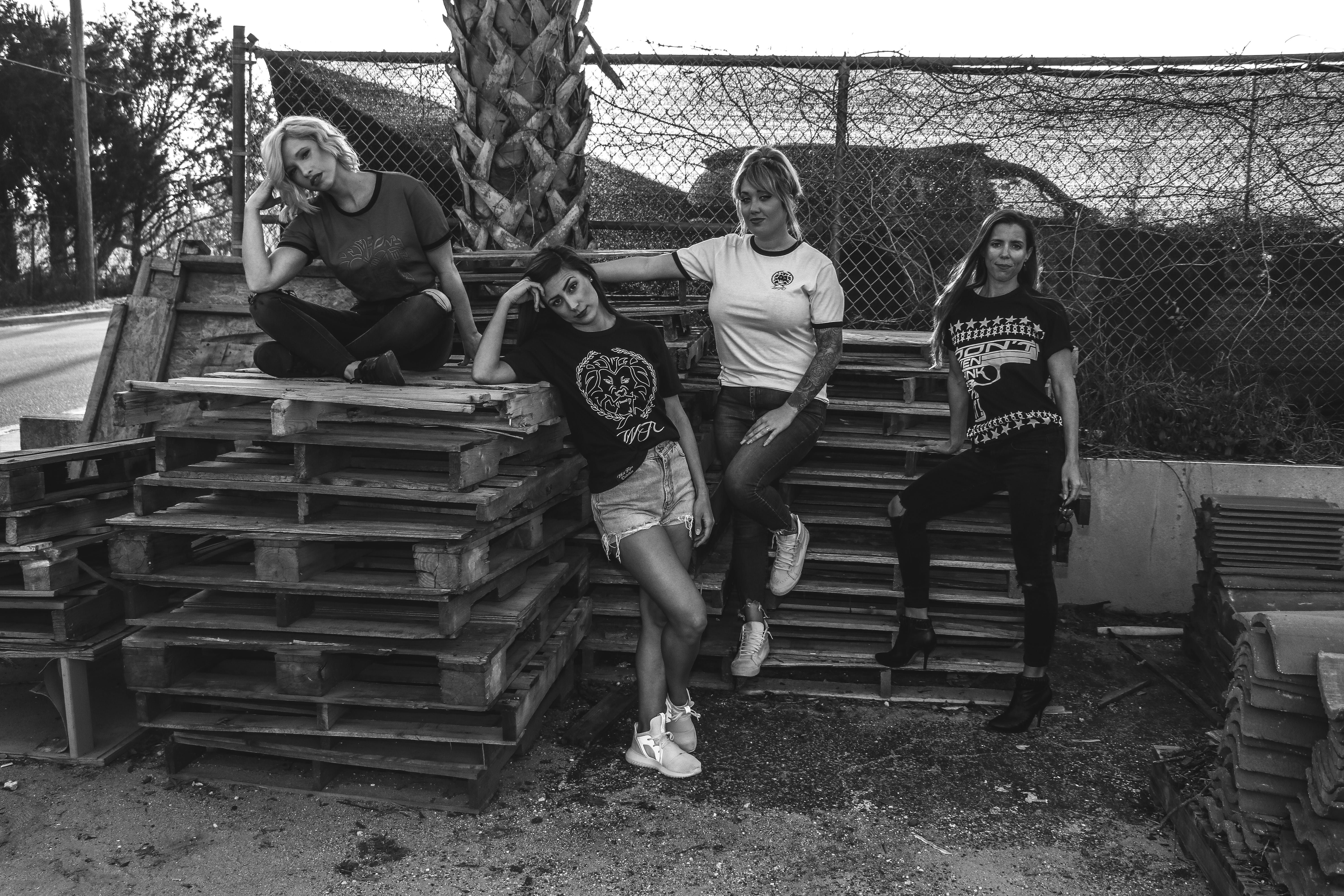 Four Women Leaning and Sitting on Pallets