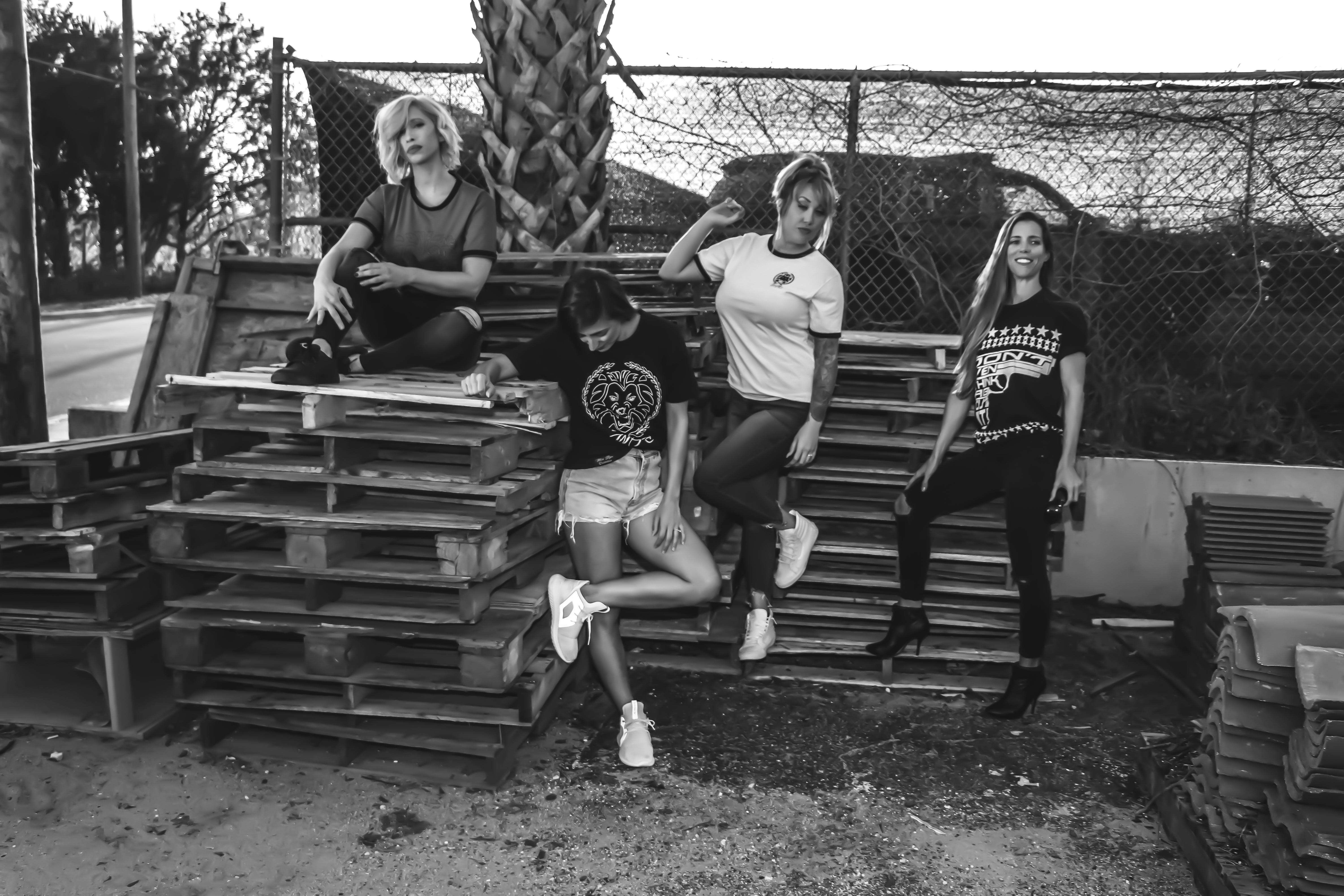 Grayscale Photo of Four Women on Wooden Pallets