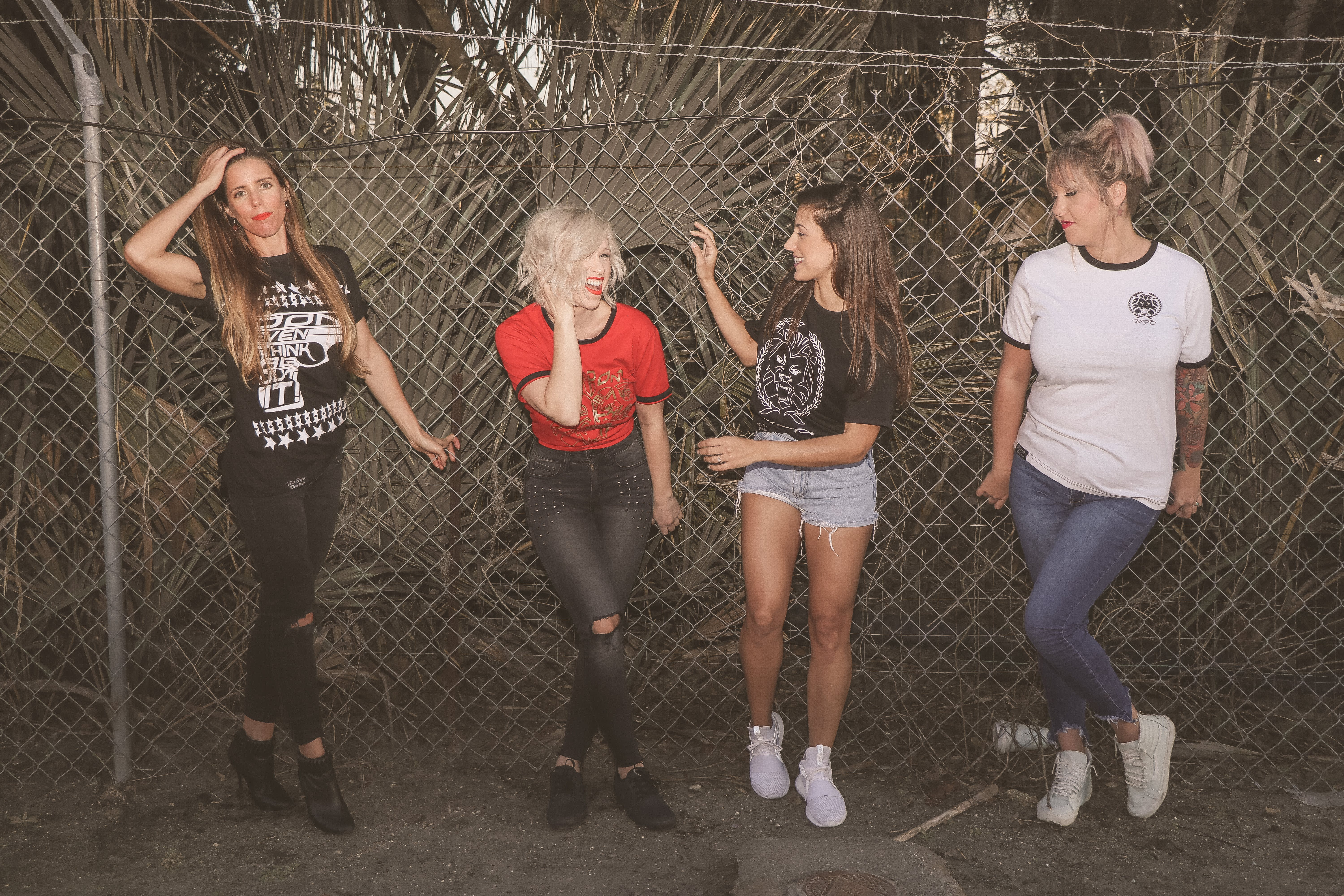Photo  of Four Women Leaning on Chain-link Fence