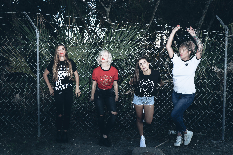 Four Women Leaning on Gray Steel Fence