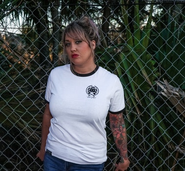 Female Wearing Black and White Crew-neck T-shirt and Blue Denim Bottoms Leaning on Chicken Wire