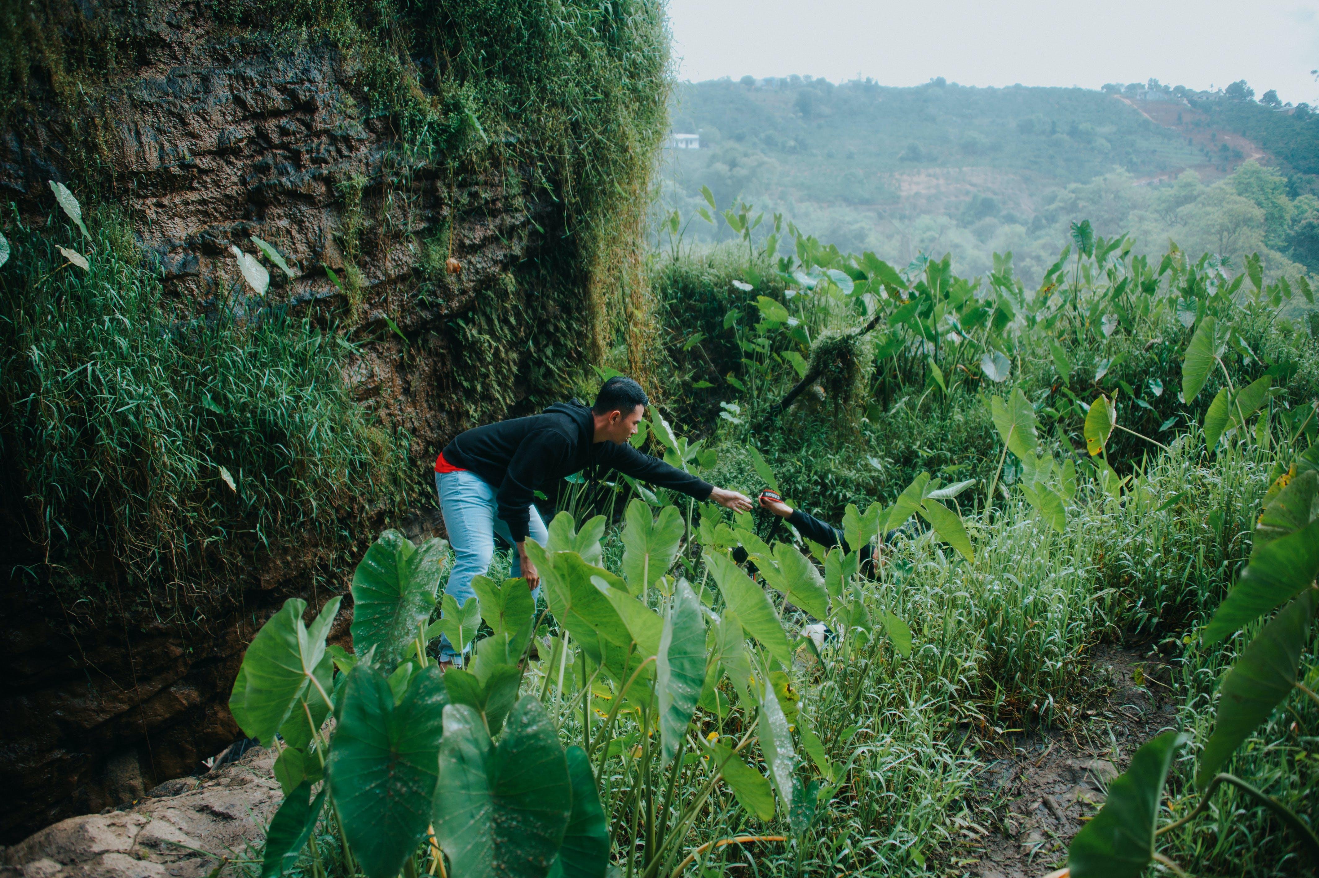 Man Wearing Black Long-sleeved Shirt and Blue Denim Bottoms