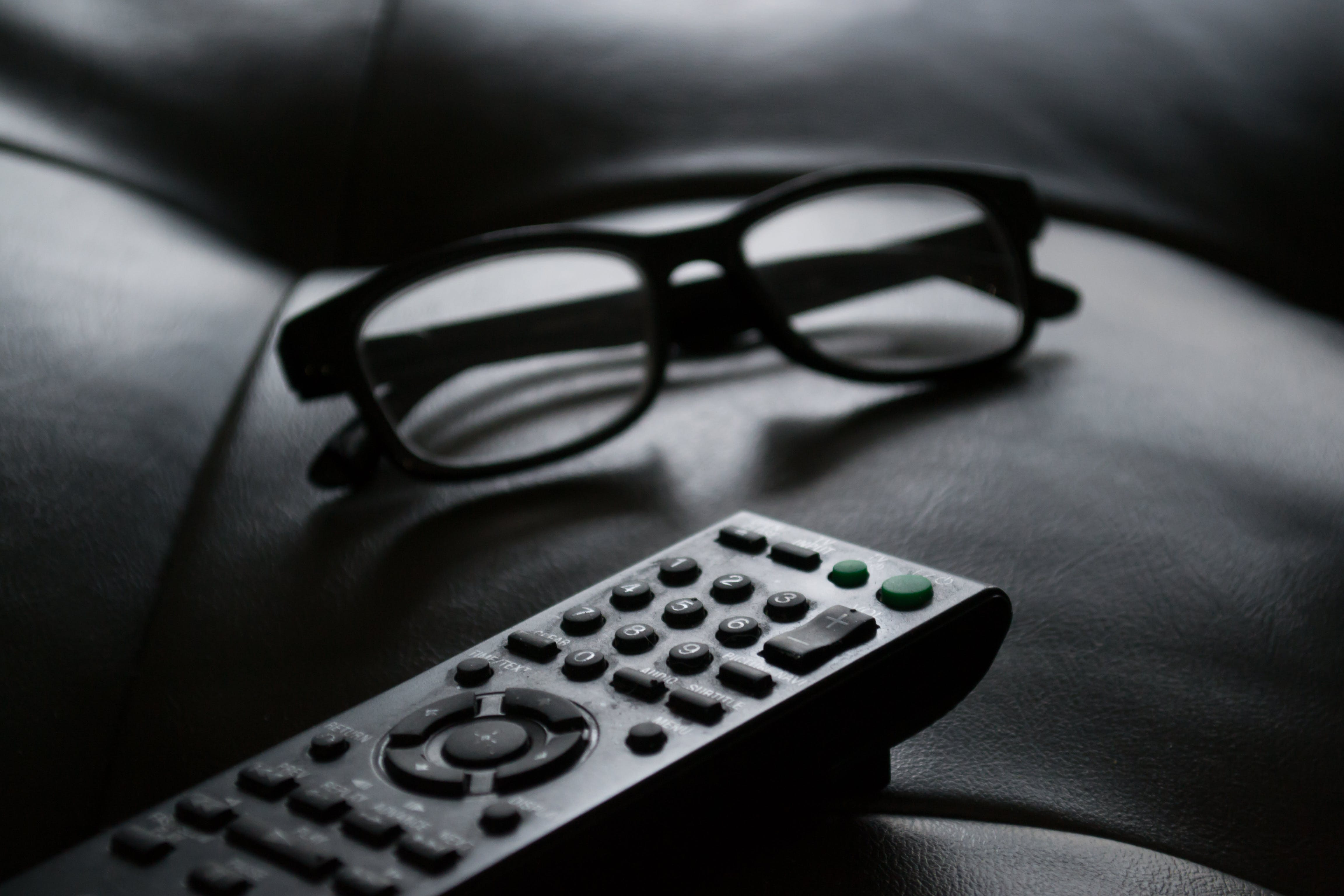 Grayscale Photo of Remote Control Near Eyeglasses