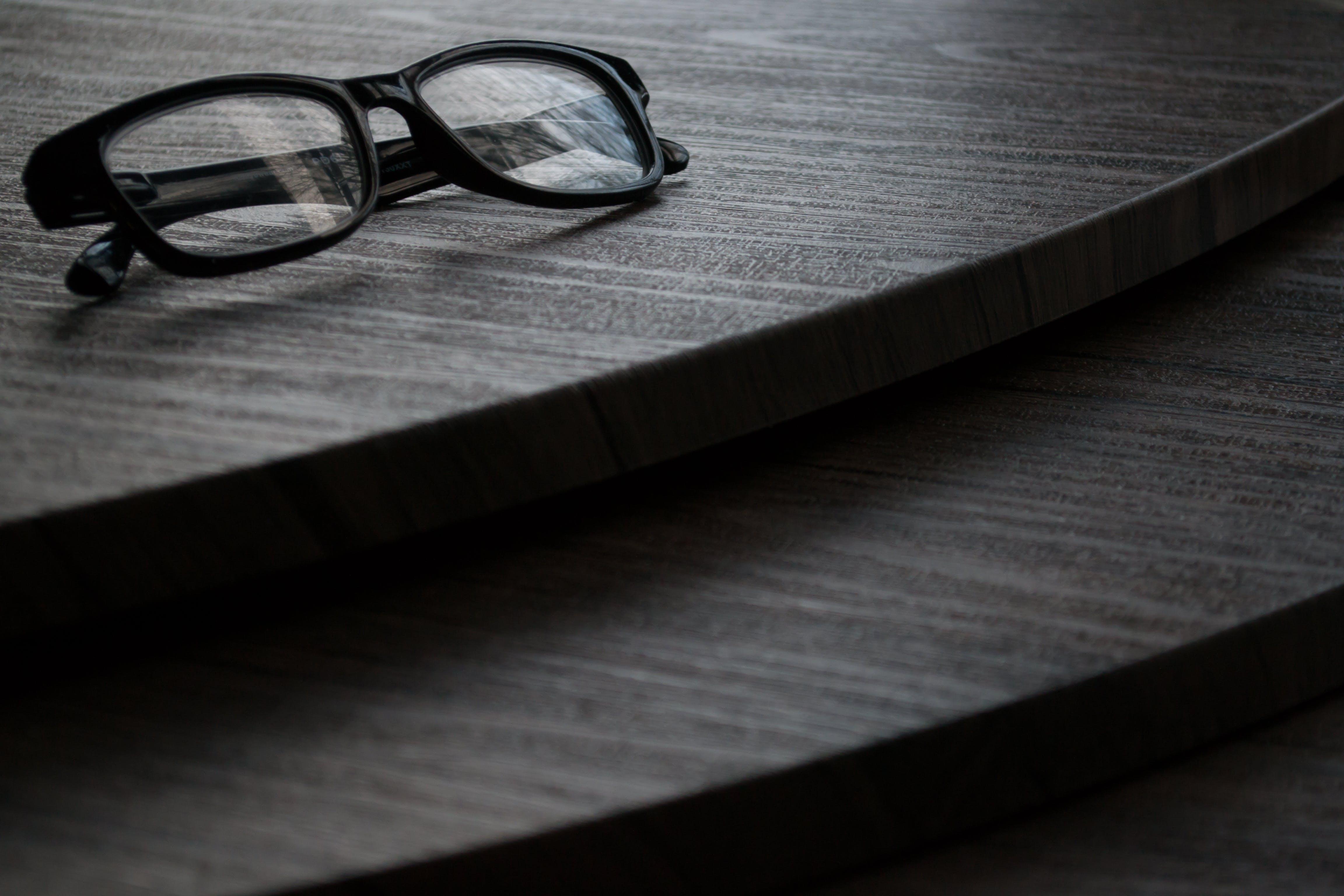 Black Framed Eyeglasses on Brown Surface