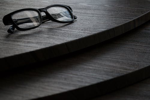 Black Framed Eyeglasses on Brown Surface