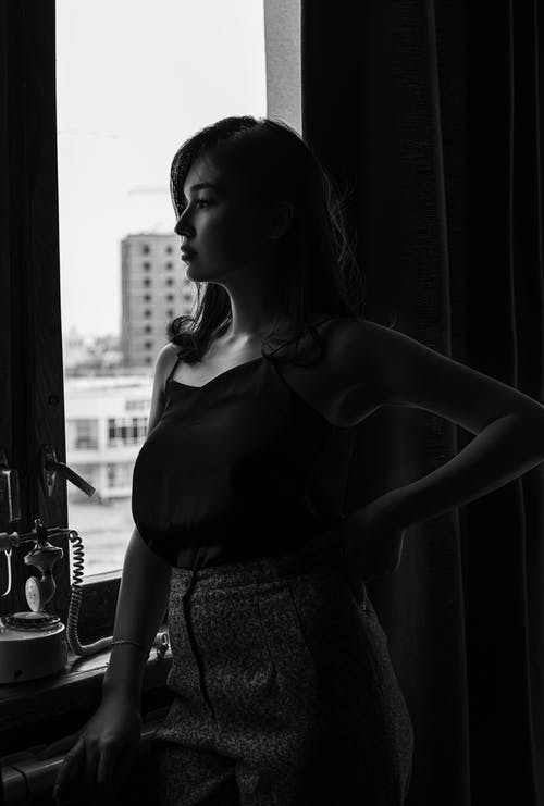 Woman in Black Tank Top and White Skirt Standing Beside Window