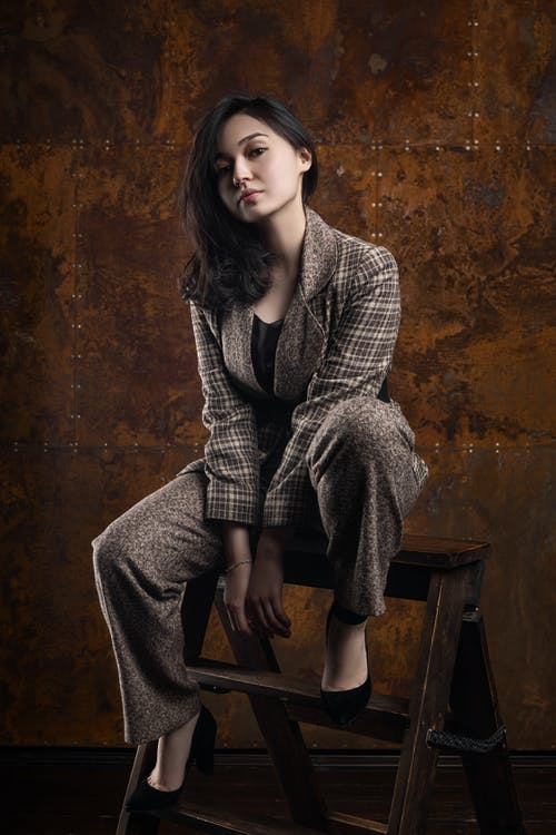 A Woman in Checkered Blazer Sitting on a Stepladder
