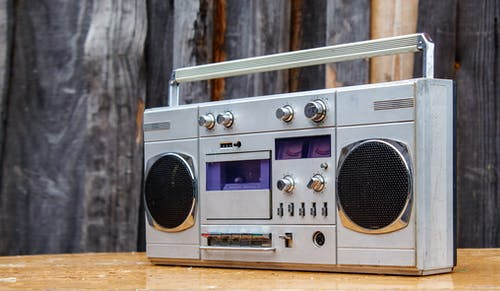A Silver Cassette Tape Player on a Wooden Table with Wooden Background