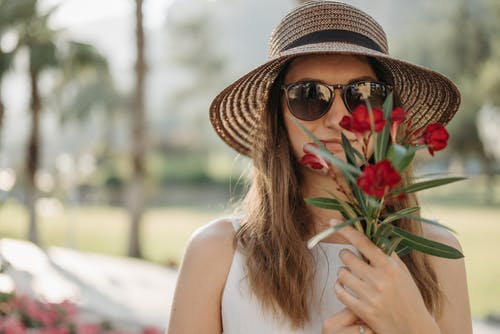 Close-Up Shot of a Woman Wearing Sunglasses Holding Red Flowers